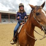 A young female rider shows off her first place ribbon after a class during a St. Vrain Roundup Club show at the Boulder County Fairgrounds.