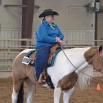 A female St. Vrain Roundup Club rider with her paint mare awaiting the judge's score in the indoor arena at the Boulder County Fairgrounds.