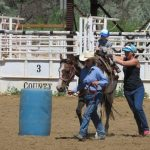 A young rider with two adult helpers tries a barrel class at a St. Vrain Roundup Club show