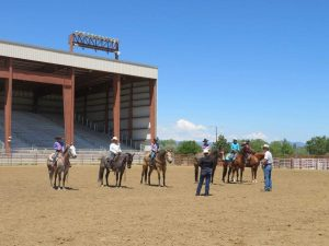 A judge addresses a class of riders at a St. Vrain Roundup Club show in the outdoor arena at the Boulder County Fairgrounds.