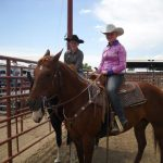 Two young riders on their horses at the outdoor arena for a St. Vrain Roundup Club show.